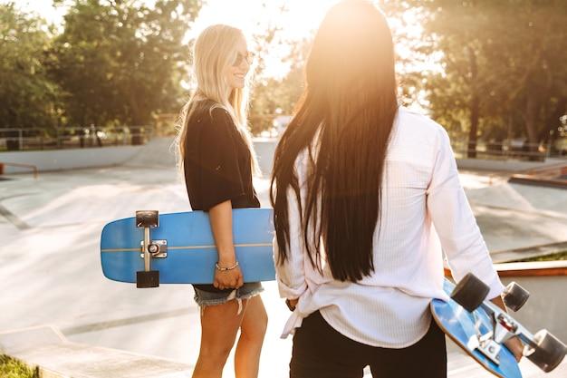 Achteraanzicht van twee aantrekkelijke jonge tienermeisjes die longboards vasthouden terwijl ze in het skatepark staan