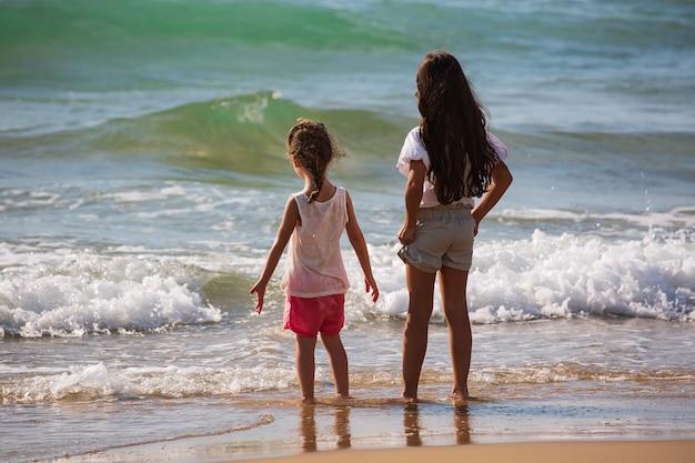 Achteraanzicht van twee amerikaanse vrolijke gelukkige meisjes die in de zee staan, korte broeken stylen en kijken naar golven naar de oceaan. zijaanzicht met kopie ruimte. kinderen spelen op het strand en de prachtige skyline.