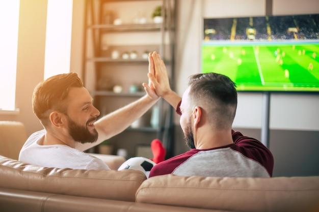Achteraanzicht van twee beste vrienden en fans van voetbal kijken naar een sportwedstrijd op de tv en bier drinken en snacks eten terwijl ze juichen voor het team op de bank