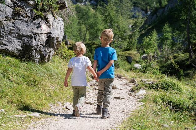 Achteraanzicht van twee broers en zussen hand in hand tijdens het wandelen op een parcours buiten in de mooie zomerse natuur.