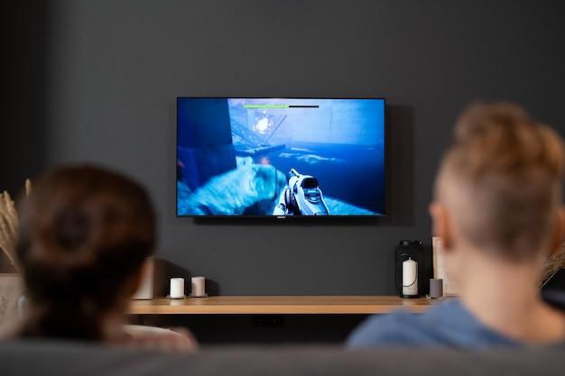 Achteraanzicht van twee hedendaagse broers en zussen die voor de tv zitten en videogames spelen in de woonkamer tijdens vakanties of in het weekend