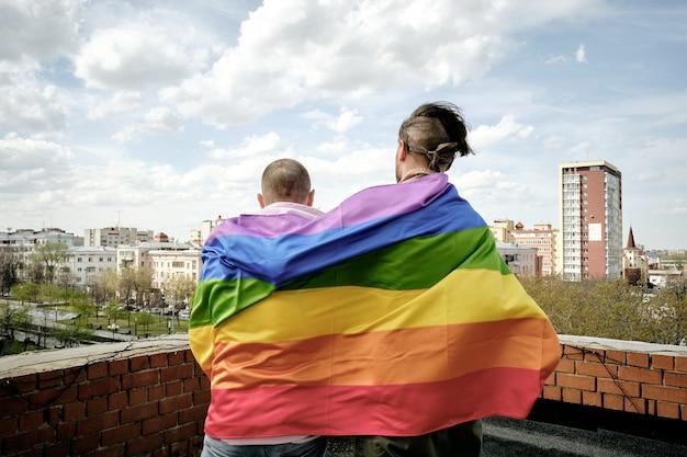 Achteraanzicht van twee homomannen verpakt in regenboogvlag
