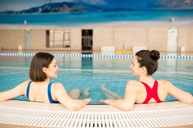 Achteraanzicht van twee jonge sportieve meisjes in badkleding rusten in het zwembad terwijl u geniet van vakantie in het resort