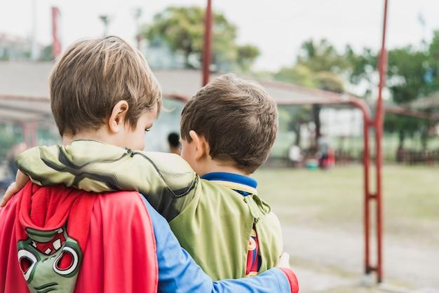 Achteraanzicht van twee kinderen in een superheld kostuum