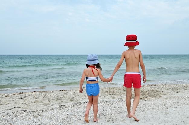 Achteraanzicht van twee kinderen, vrienden, wandelen op het strand, hand in hand. broer en jongere zus in badkleding op de achtergrond van de blauwe zee. zomervakantie concept