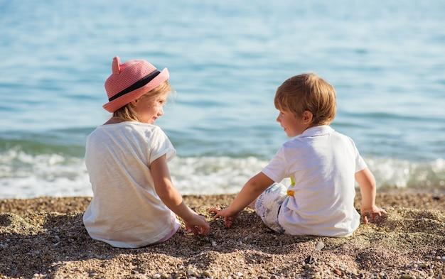 Achteraanzicht van twee kinderen zittend op stenen. kleine reizigers bij de oceaan. zomervakantie concept. reizende achtergrond