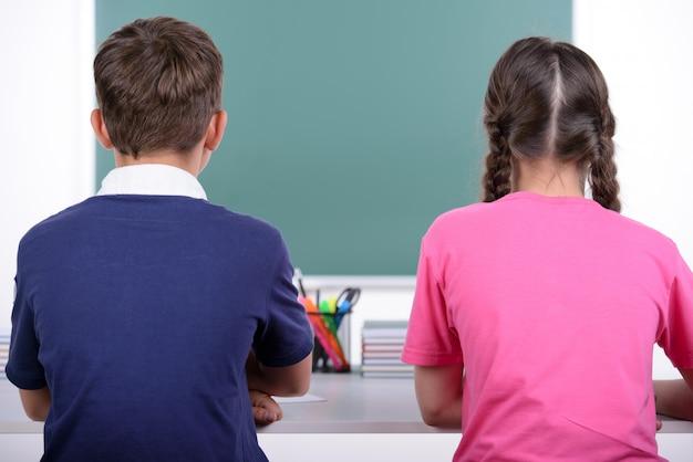 Achteraanzicht van twee kleine klasgenoten die samen een boek lezen.
