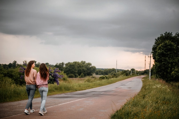 Achteraanzicht van twee meisjes met een groot boeket wilde violette lupines, gekleed in vrijetijdskleding wandelen