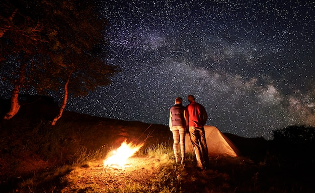 Achteraanzicht van twee personen klampt zich vast aan elkaar kijken naar sterrenhemel met melkweg