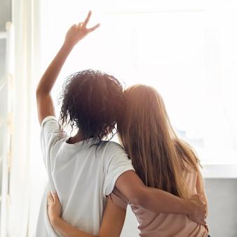 Achteraanzicht van twee vriendinnen knuffelen voor het raam