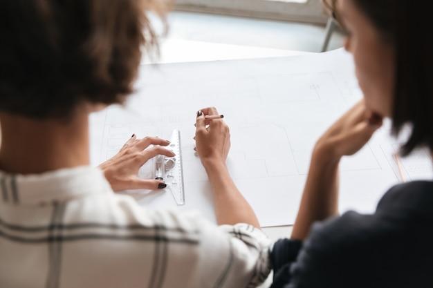 Achteraanzicht van twee vrouwen die werken bij de tafel
