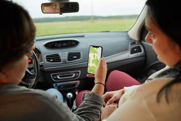Achteraanzicht van twee vrouwen kijken naar online kaart op mobiele telefoon tijdens het besturen van de auto