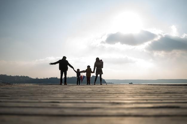 Achteraanzicht van vader en moeder met kinderen hand in hand