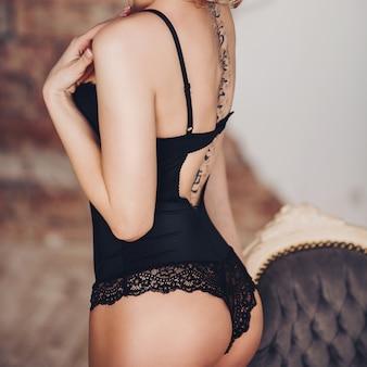 Achteraanzicht van verleidelijke vrouw in zwart kantlichaam met tatoeage.
