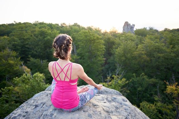 Achteraanzicht van verlicht door zomerzon jonge slanke toeristische vrouw zittend op de top van enorme rots yoga oefening op groene bomen boven bos achtergrond doet