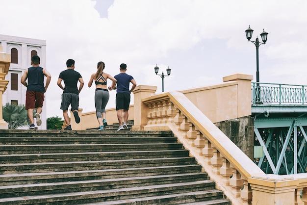 Achteraanzicht van vier mensen in sportkleding joggen boven in het centrum van de stad