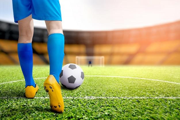 Achteraanzicht van voetballer man schoppen de bal
