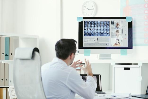 Achteraanzicht van volwassen mannelijke arts zittend aan de tafel en kijken naar computermonitor met x-ray beelden en ze online bespreken met collega's