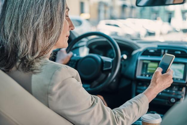 Achteraanzicht van volwassen mooie vrouw in slimme vrijetijdskleding met behulp van telefoon tijdens het autorijden