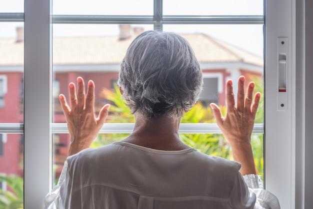 Achteraanzicht van volwassen vrouw met grijze haren die uit het raam kijkt met de handen op glas