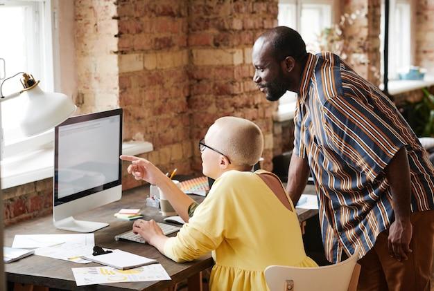 Achteraanzicht van volwassen zakenvrouw wijzend op computermonitor en bespreken met zakenman online document terwijl ze op kantoor werken