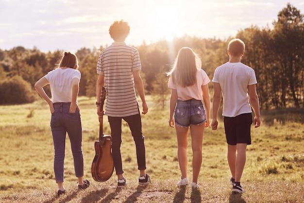 Achteraanzicht van vriendelijke klasgenoten die bij zonnig weer buiten recreëren, over weide wandelen, gitaar gebruiken om liedjes te zingen, langzaam wandelen, gekleed in vrijetijdskleding. mensen en recreatie concept