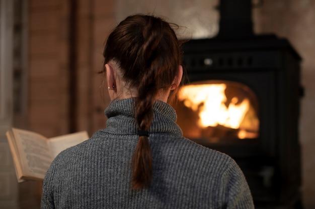 Achteraanzicht van vrij lang haar brunette vrouw met vlecht in grijze trui lezing bij open haard