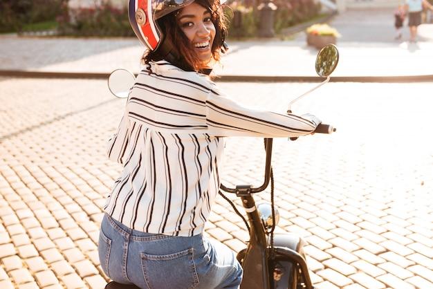 Achteraanzicht van vrolijke afrikaanse vrouw in moto halmet ritten op moderne motor buitenshuis en kijken naar de camera