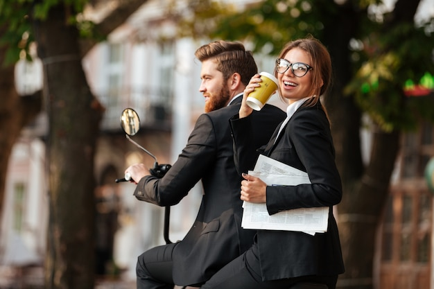 Achteraanzicht van vrolijke elegante paar rijdt op moderne motor
