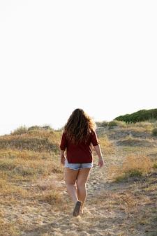 Achteraanzicht van vrouw buiten lopen in de natuur