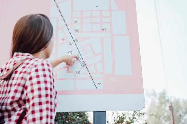 Achteraanzicht van vrouw die een kaart controleert