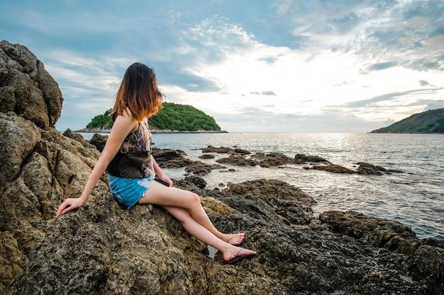 Achteraanzicht van vrouw die het overzees in de de zomertijd ziet