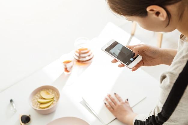 Achteraanzicht van vrouw die moderne foto's op de telefoon.