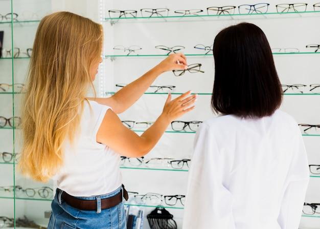 Achteraanzicht van vrouw en opticien in winkel