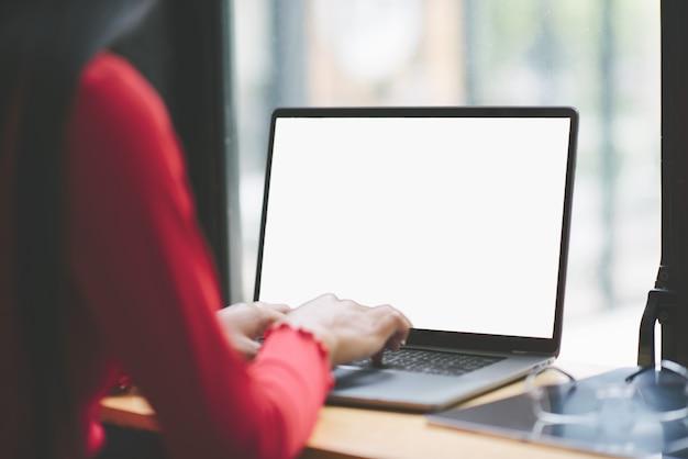 Achteraanzicht van vrouw freelancer werkt aan een nieuw project op laptopcomputer.