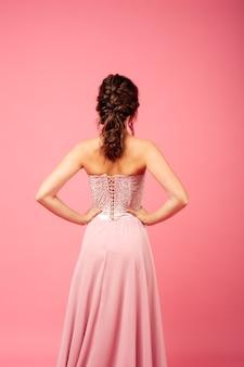 Achteraanzicht van vrouw in delicate roze korset jurk met veter en kant geïsoleerd op roze background