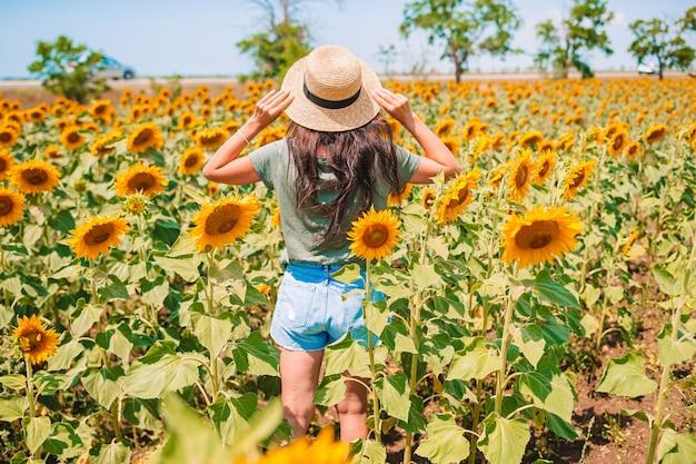 Achteraanzicht van vrouw in een strooien hoed in een veld met zonnebloemen. zomertijd.