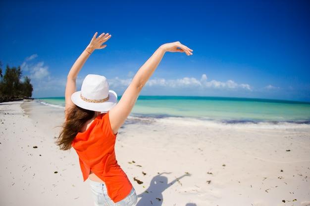 Achteraanzicht van vrouw in hoed tijdens tropische strandvakantie