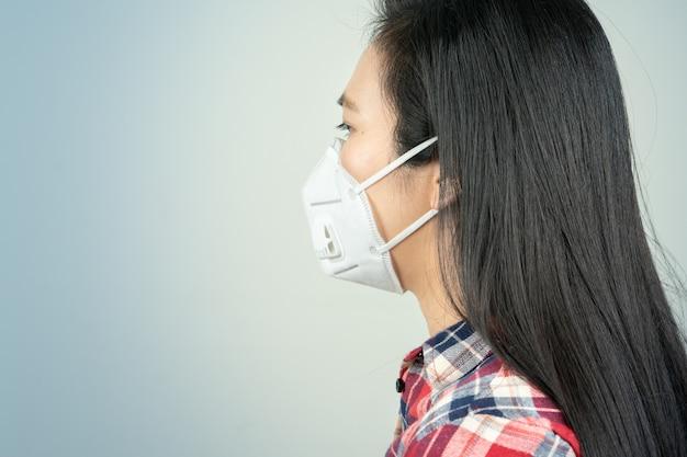 Achteraanzicht van vrouw in masker vanwege luchtverontreiniging en epidemie in de stad. bescherming tegen virussen, infecties, uitlaatgassen en industriële emissies
