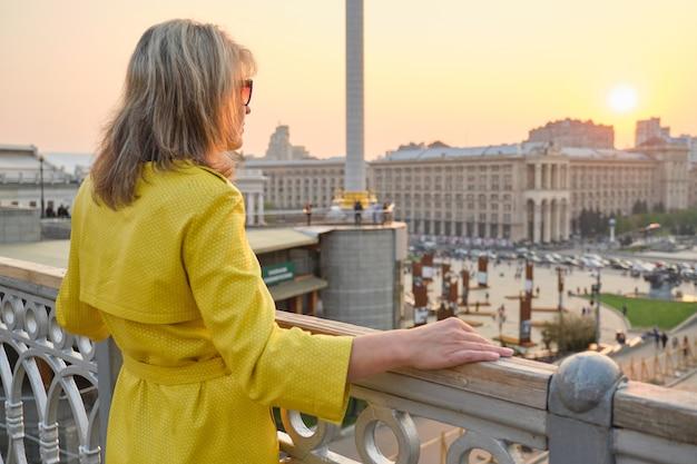Achteraanzicht van vrouw kijken naar panorama van stad zonsondergang