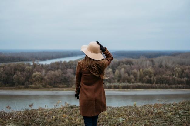 Achteraanzicht van vrouw met hoed het uitzicht op het meer bewonderen