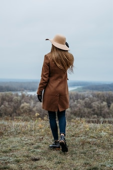 Achteraanzicht van vrouw met hoed poseren in de natuur buitenshuis