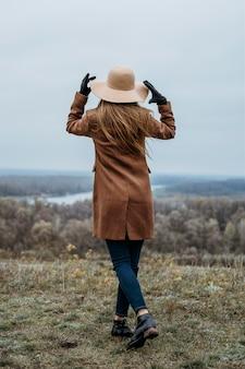 Achteraanzicht van vrouw met hoed poseren in de natuur