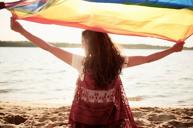 Achteraanzicht van vrouw met regenboogvlag op het strand