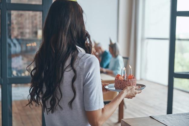 Achteraanzicht van vrouw met verjaardagstaart terwijl gasten wachten in de woonkamer
