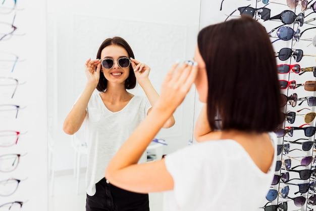 Achteraanzicht van vrouw probeert zonnebril