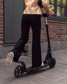 Achteraanzicht van vrouw rijden elektrische scooter buitenshuis