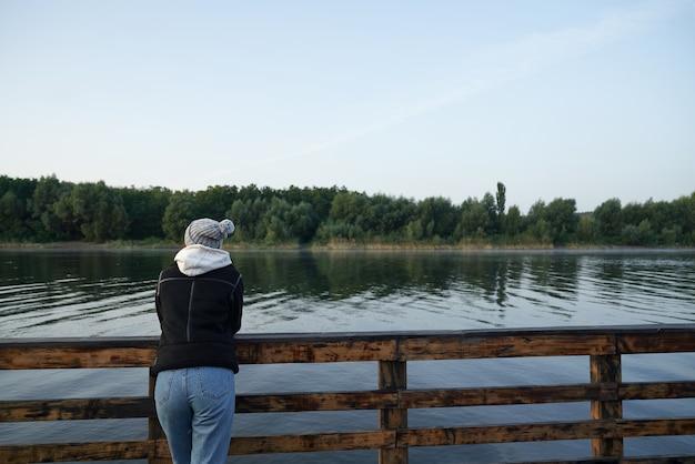 Achteraanzicht van vrouw staande pier in de buurt van meer