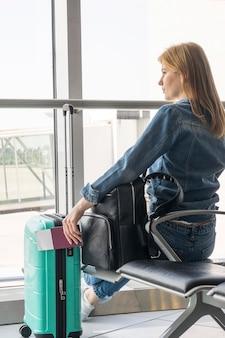 Achteraanzicht van vrouw te wachten in de luchthaven