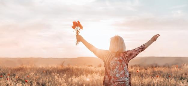 Achteraanzicht van vrouw toerist met rugzak en papaver bloemboeket bij zonsondergang in het veld. zomervakantie. gelukkig meisje dat van de zon geniet. horizontale banner